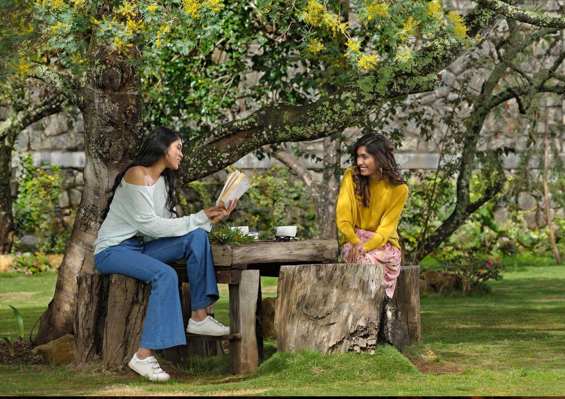 Young-woman-enjoying-nature-with-book-and-coffee